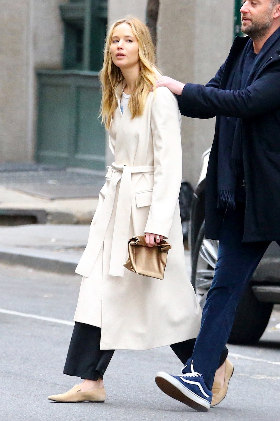 Jennifer Lawrence Minimalist Outfit — White Belted Coat, Satin Alexander Wang Lunch Bag Clutch, Black Wide-Leg Pants, and The Row Tan Suede Loafers