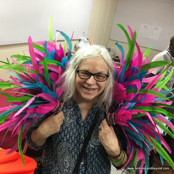 travel writer Carole Terwilliger Meyers models feather costume at Ronnie of Ronnie & Coro Mas Camp costumes in Port of Spain, Trinidad