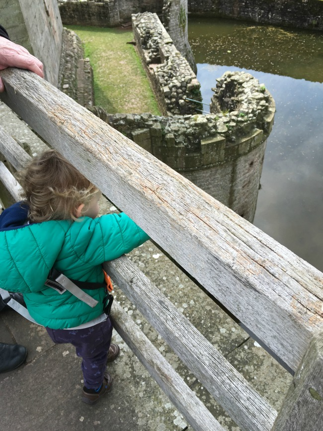 toddler on bridge over moat pointing