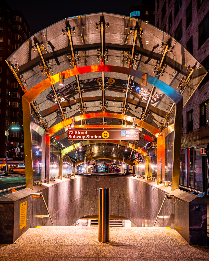 a photo of an entrance to the q subway station in new york city at night
