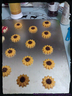 Cookie sheet of sunflower shaped cookies with chocolate sprinkles in the centers to imitate the seeds of a sunflower.
