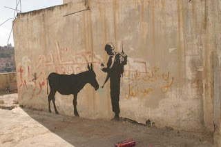 A donkey being checked by soldier - Banksy