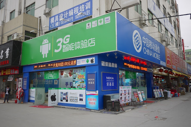 Store in Nanping, Zhuhai, China displaying signs with logos for Android, Apple, Nokia, and more.