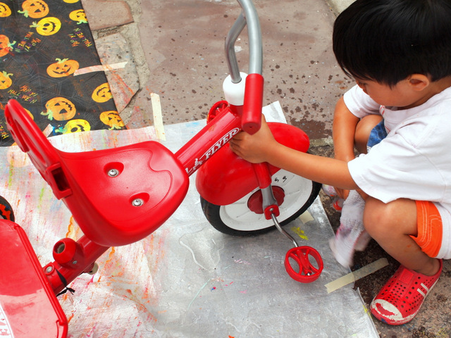 boy cleaning tricycle after painting with it