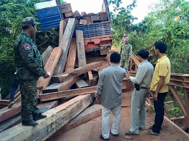 People inspect the damage to a ruined bridge last week in Kampot province after an overloaded logging truck tried to pass over it. National Police