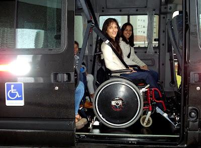 A imagem mostra em detalhe uma mulher, de perfil, sentada em uma cadeira de rodas voltada para a direita, mesmo sentido de marcha do veículo. A mulher está com o cinto de segurança afivelado. Ela é branca, tem cabelos castanhos longos e lisos, veste blusa de manga longa branca e calça jeans azul índigo. A cadeira de rodas está sobre os trilhos de ancoragem e o sistema de travamento está acionado. Na janela oposta há uma mulher sentada em outra cadeira de rodas acoplada ao sistema de ancoragem. Ela é morena, tem cabelos castanho-escuros lisos e com cachos nas pontas, na altura dos ombros. Também está com o cinto de segurança afivelado e veste blusa branca de manga longa e calça jeans.Fim da descrição