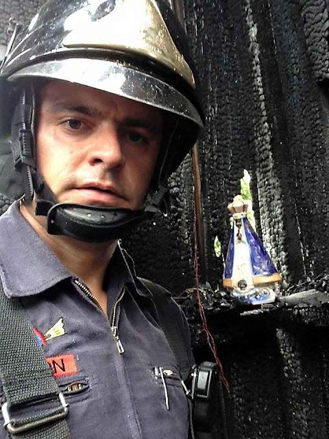 O bombeiro Anderson Batista junto à Imagem intocada pelo fogo em Dracena SP