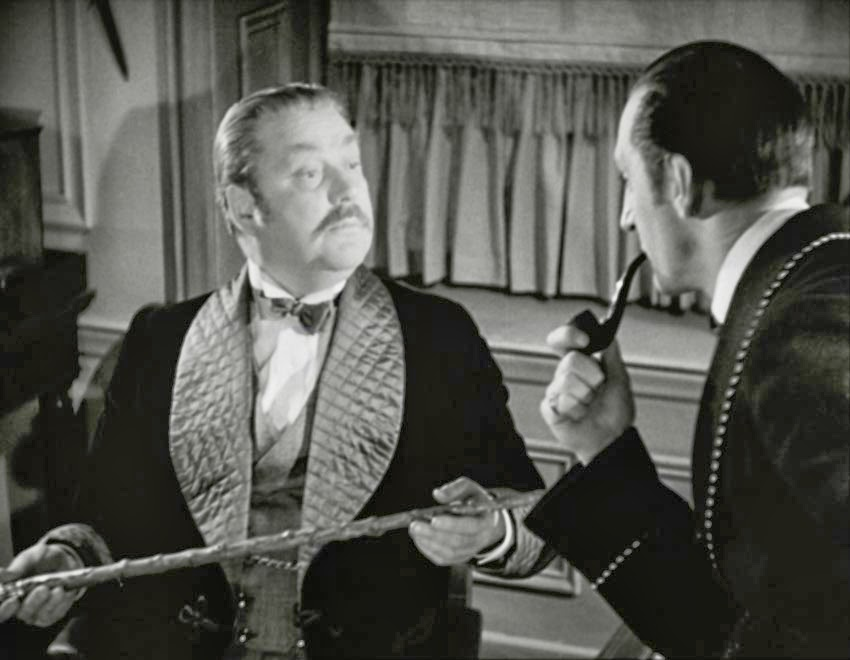 Dr. Watson (Nigel Bruce), examining Dr. Mortimer's stick left behind in The Hound of the Baskervilles, as overseen by Sherlock Holmes (Basil Rathbone)