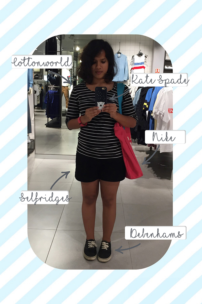 An image of a young woman in a striped tshirt, black shorts, black sneakers and pink tote taking a selfie in a clothing store mirror