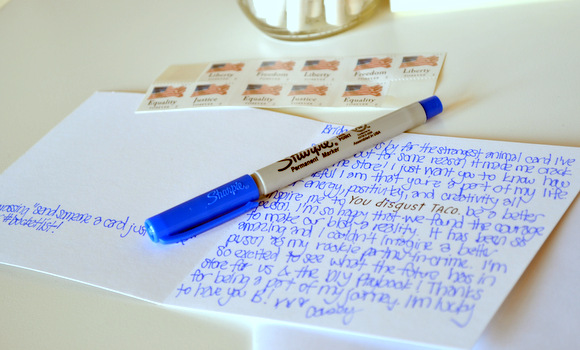 Greeting card with postage and pen