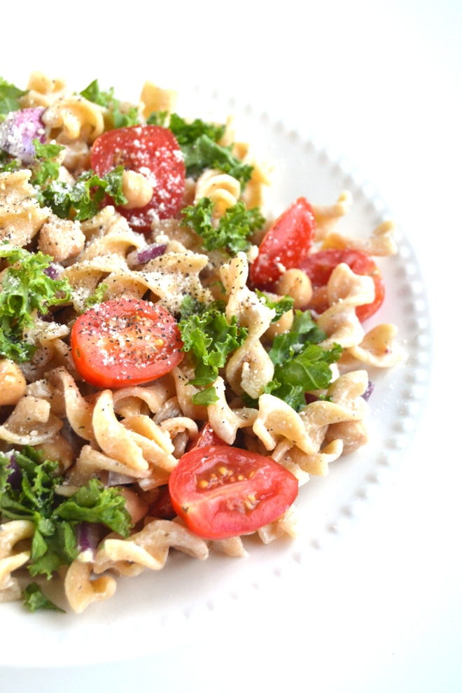 This Kale Caesar Pasta Salad is so simple to make and is full of flavor and nutrients! Filled with whole-wheat noodles, kale, tomatoes, red onion and garbanzo beans. www.nutritionistreviews.com