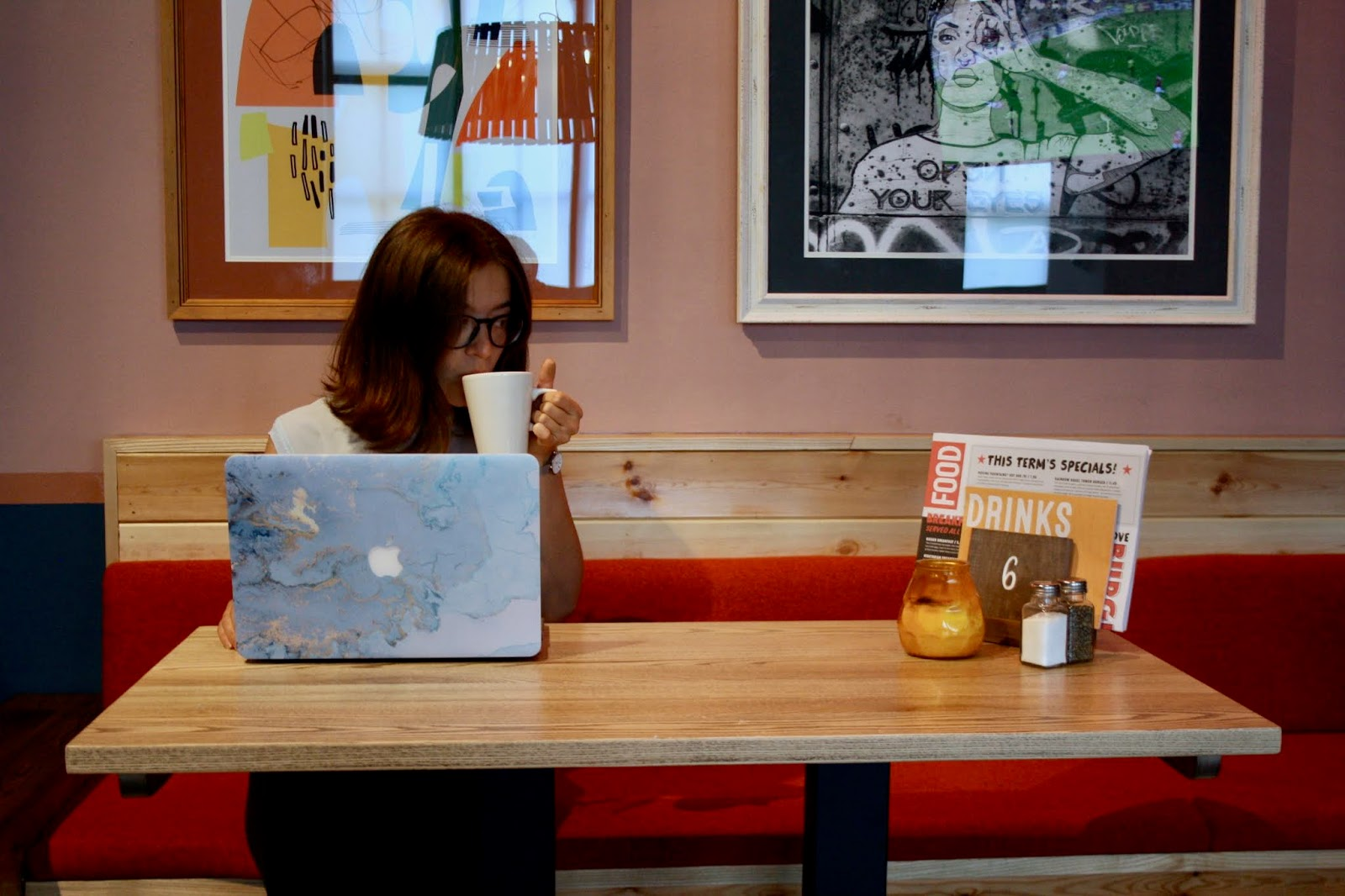 Abbey sits at a table at a cafe with her laptop, sipping from a coffee cup