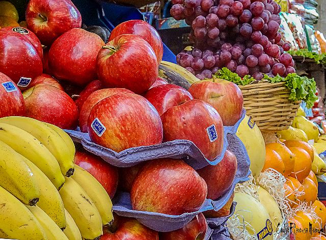 Puesto de frutas con manzanas rojas  bananas y uvas.