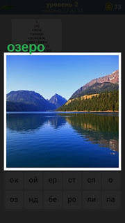 Голубое озеро, в котором отражение холмов и леса