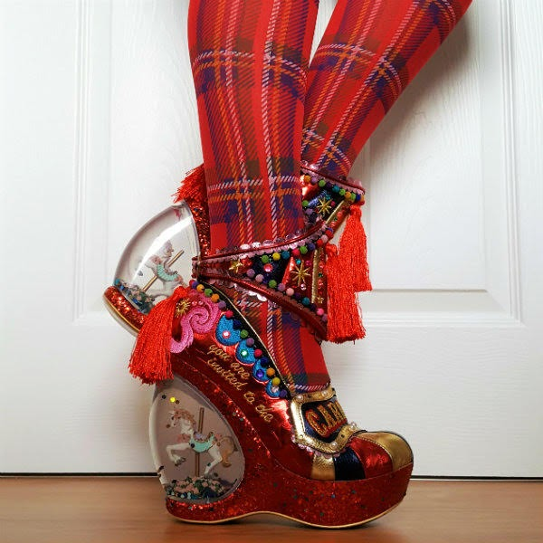 raised and straight leg wearing carousel circus themed shoes with snowglobe heel
