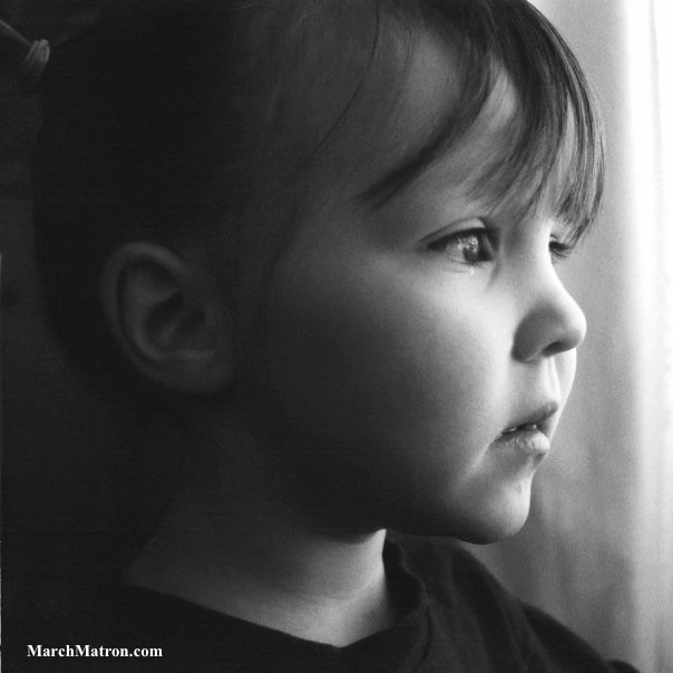 Beautiful black and white photo toddler looking out the window snow day