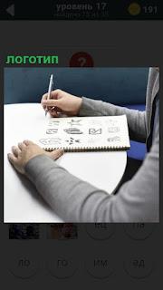 За столом на бумаге мужчина рисует несколько логотипов