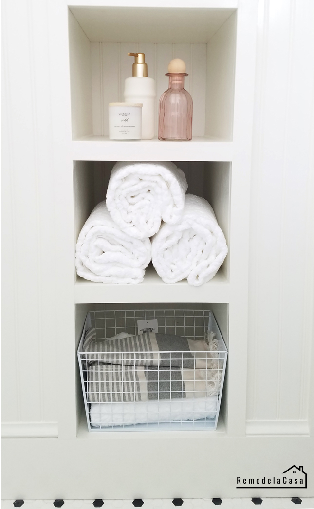 Towels and bath products in bathroom shelf