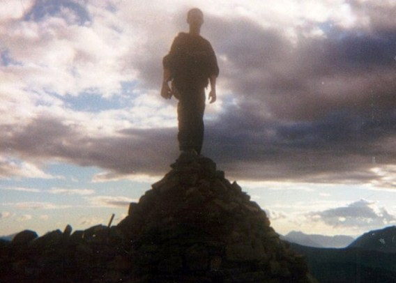 A man standing on the summit of a scottish mountain as it gets dark