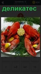 На тарелке лежат деликатесы в виде лобстеров, зелени и лимона, нарезанного дольками