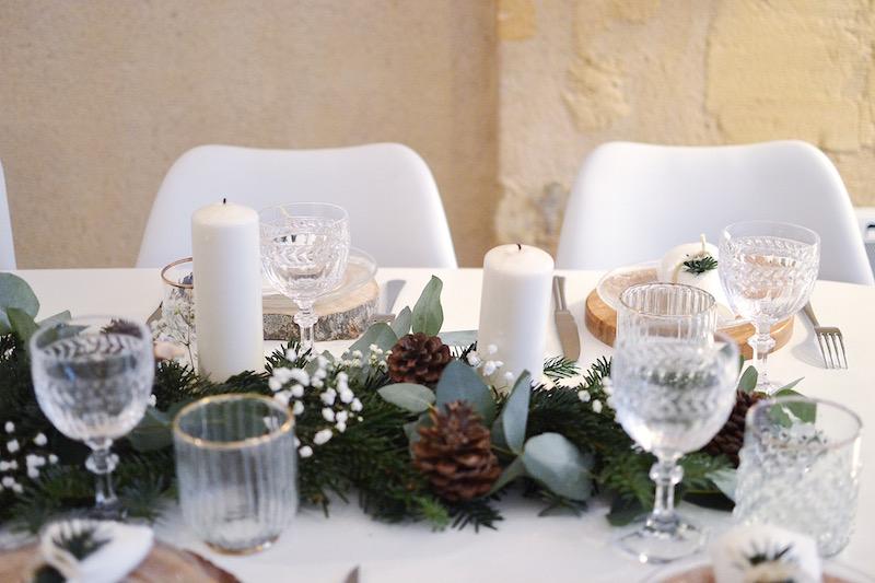 rondin de bois, assiette en verre maisons du monde, serviette blanche et branche de sapin, chaise blanche maisons du monde