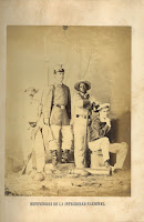 "A tipped-in full-page photograph following page 32 of the book, with the caption ""Defensores de la Integridad Nacional."" The photograph depicts four different types of soldier, all in different uniforms. The soldier on the far right is seated and seems to be a sailor given his distinctive hat. The soldier third from the left is of African descent while the other three appear to be Spanish. on the ground in front of the men lie a cannon and several cannonballs."