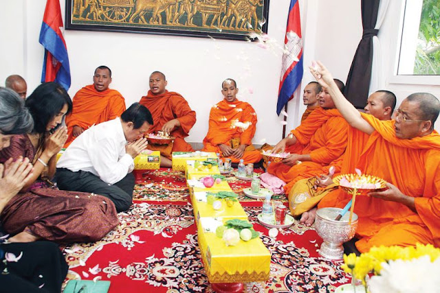 Kem Sokha (left), CNRP acting president, receives a Buddhist blessing at party headquarters on Monday. Yesterday, Sokha was summonsed to court over a motion filed by his attorney. Facebook