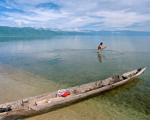Tinuku Travel Lake Poso white golden sandy beach and green blue water surrounded by hills and orchids forest