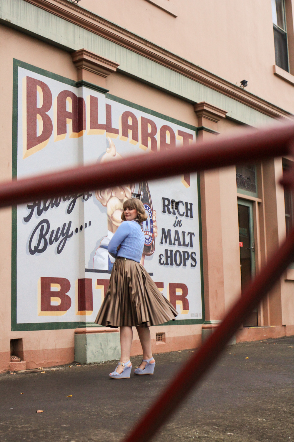 Liana of @findingfemme in gold ASOS pleated skirt at vintage Ballarat Bitter sign