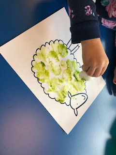girl's hand holding cotton ball with green paint over sheep outline