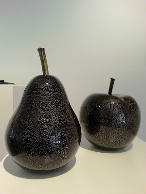 Large black and gold pear and apple on display in a gallery.