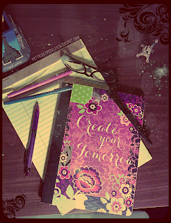 Image of a yellow legal pad & a purple floral composition book sitting on a wooden desk surface.  Pens and a pair of seeing glasses are strewn over them.  Two(2) Eiffle Tower themed ornaments on sides of the books.  Stars and faded bubbles fogged over image.  Composition booklet reads: Create Your Tomorrow