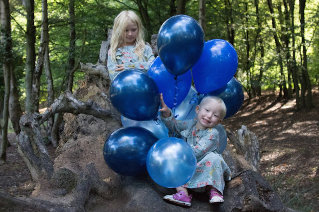 Sitting on an uprooted tree with a bunch of balloons still not looking at the camera