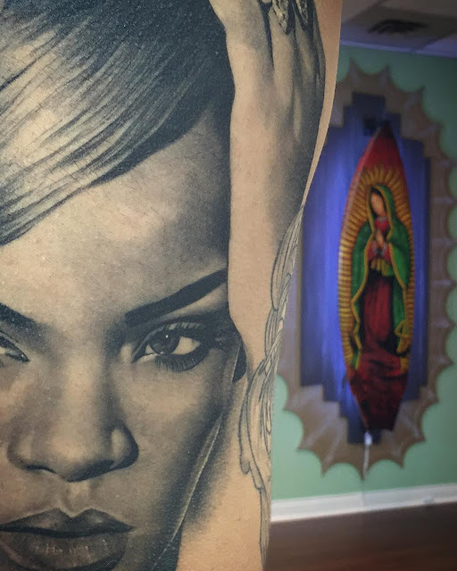 a cool tattoo of Rihanna's face done on a girl's back