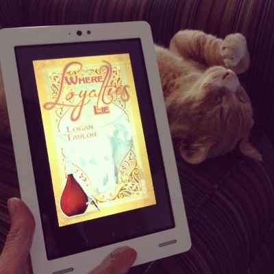 Ollie flops on his back in a beige and green striped chair, his paws in the air. In front of him is a white Kobo with the cover of Where Loyalties Lie on its screen. The cover features two indistinct, pale green silhouettes in what might be a romantic embrace. Gold filigree borders the figures, and a clear glass carafe of red wine rests in the left hand corner, as if perched on the edge of the border.