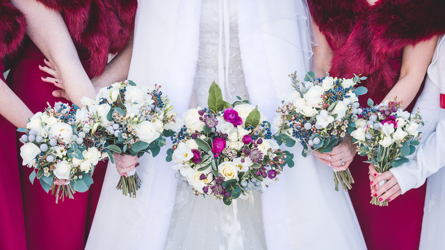 Bride holding bouquet with her bridesmaids red and white contrast