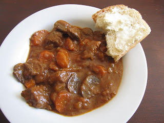 beef stew in a white bowl with a slice of bread and butter
