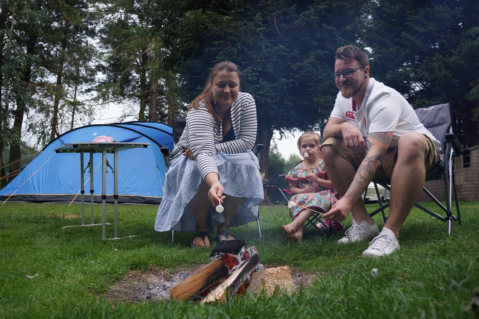 mum, dad and daughter sitting by campfire