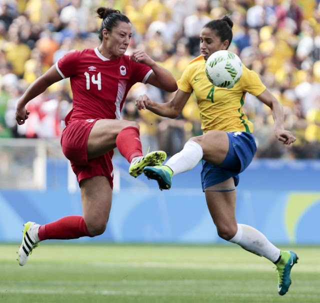 Rafaelle of Brazil vies for the ball with Melissa Tancredi of Canada