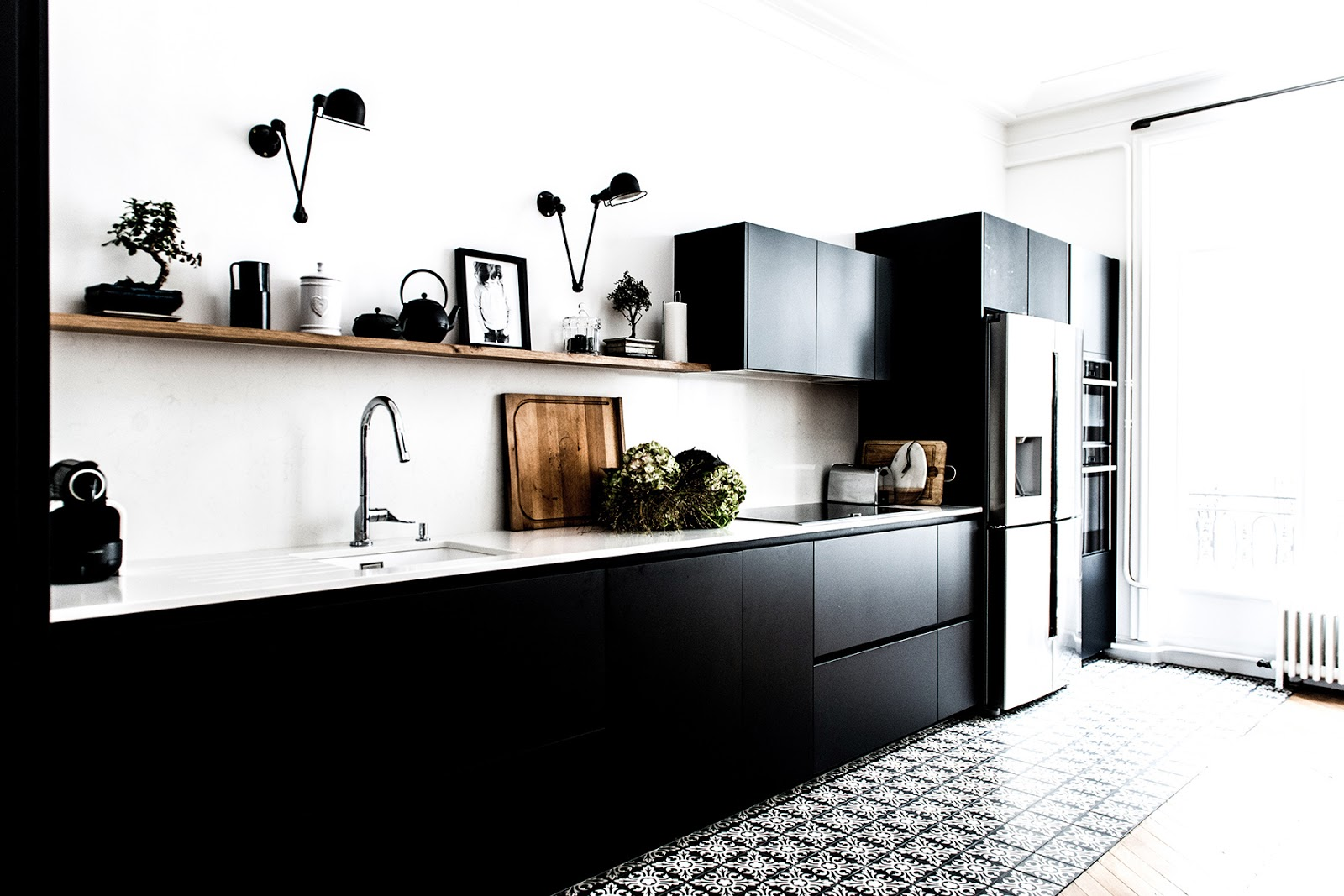 black kitchen with a white work top and wood shelfs