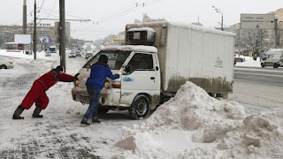 Men push a vehicle after a heavy snowfall in Moscow, Russia, Feb. 5, 2018 (Credit: voanews.com) Click to Enlarge.