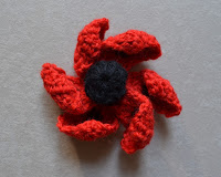 """Oriental Poppy"" by Lesley Stanfield before blocking. The six petals have curled inwards over themselves, looking like a windmill."