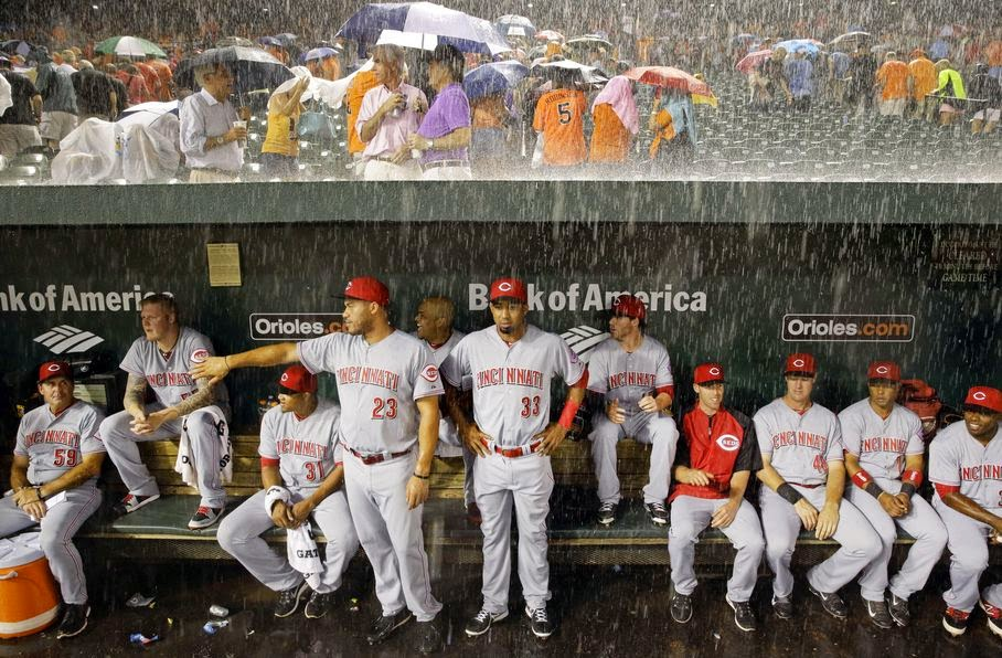 Members of the Cincinnati Reds watch from the dugout as heavy rain falls during a rain delay in the first inning of an interleague baseball game against the Baltimore Orioles, Tuesday, Sept. 2, 2014, in Baltimore.