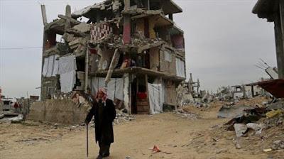 Un anciano palestino pasa por un edificio destruido en la guerra israelí contra la Franja de Gaza.
