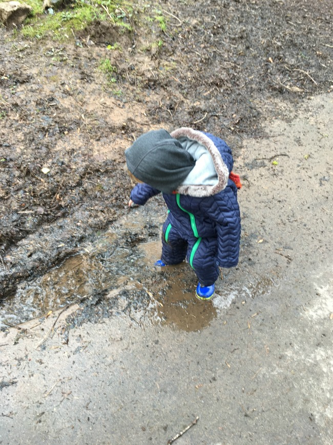 toddler paddling in muddy puddle