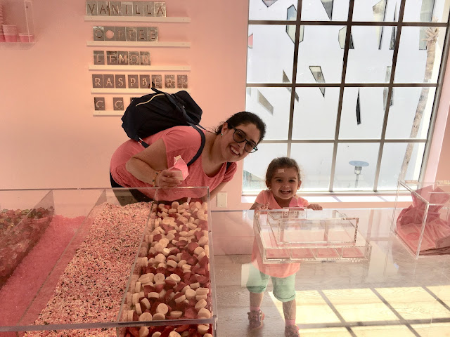 Mother and daughter posing for a photo by a fake toppings bar art installation