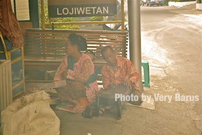 Sepasang suami istri ngamen di depan warung sate