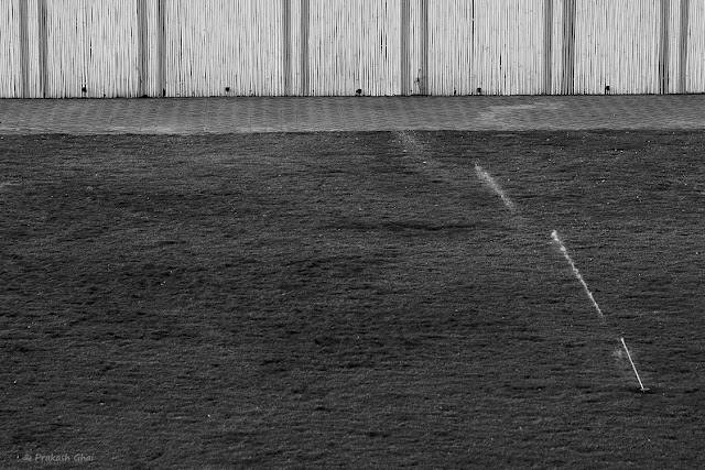 Black and White Minimalist Photography using Water Sprinkler and Empty Garden field as a Subjects.