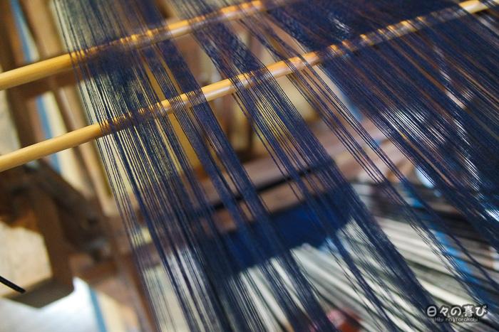 fils indigos tendus sur un métier à tisser