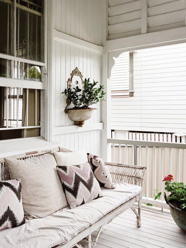 sofa de mimbre con cojines bajo el porche chicanddeco